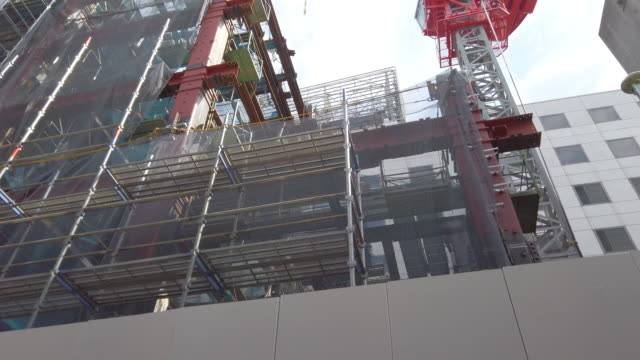 4k low angle view tilt up .construction cranes and construction site in tokyo , japan . - construction material stock videos & royalty-free footage