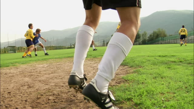 low angle view tracking shot of goalkeeper's feet / sliding to make save - studded stock videos and b-roll footage