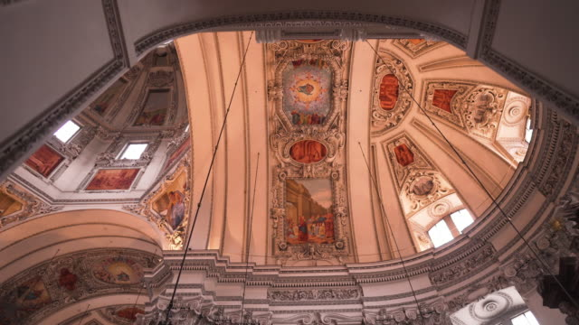 low angle view: walking in the church to see an interior view of salzburg cathedral, the baroque cathedral of the roman catholic archdiocese of salzburg in the city of salzburg, salzburg, austria. - arco architettura video stock e b–roll
