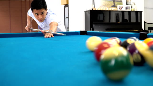 low angle view: young man playing billiard in a pool hall - pool hall stock videos and b-roll footage