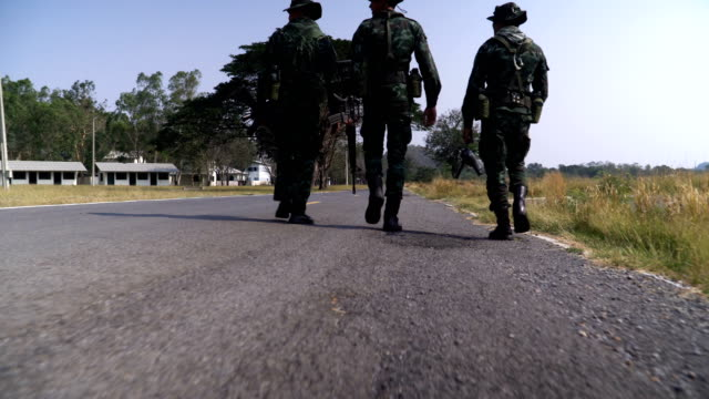 low angle view:following group of fully Equipped and Armed Soldier walking on the road