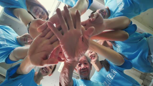 low angle view, happy le persone del gruppo asiatico mettono le mani insieme di volontari della comunità e mani in un huddle prima del progetto della comunità. amicizia, lavoro di squadra, successo, volontariato, beneficenza, leadership, persone, anziani - beneficenza video stock e b–roll