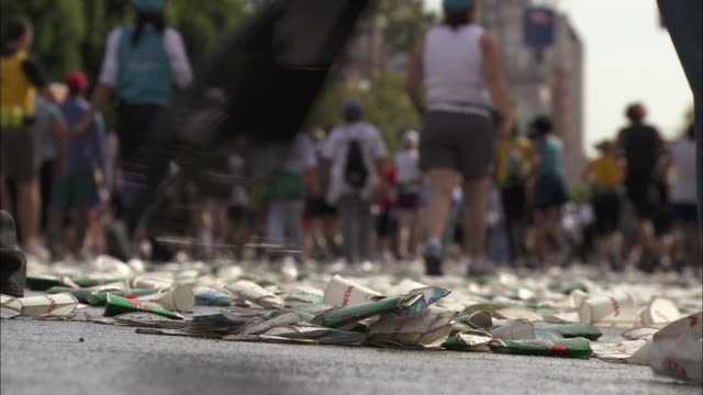 Low Angle  - Volunteers rake up used paper cups and other litter during a marathon/Hollywood, California, USA