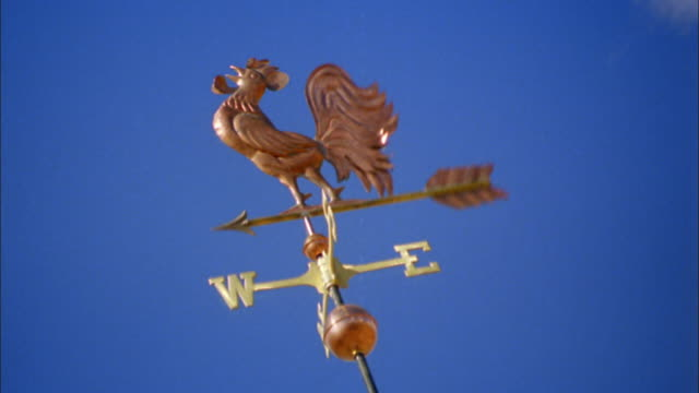 vidéos et rushes de canted low angle ms weather vane spinning with clear sky in background / new england - tourner