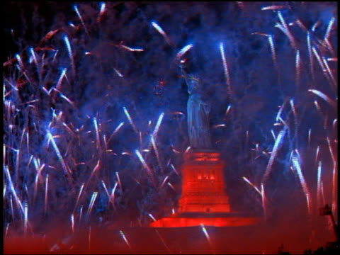 low angle wide shot abundance of fireworks shooting into sky around statue of liberty at night / new york city - fourth of july stock videos & royalty-free footage