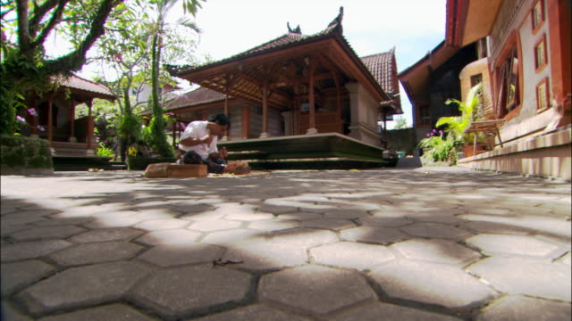 Low angle wide shot Balinese mask maker Ida Bagus Anon carving mask in courtyard in Ubud / Bali, Indonesia