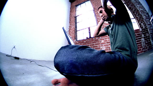Low angle wide shot barefoot man sitting with laptop on crossed legs, pressing hands against head and screaming
