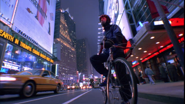 Low angle wide shot bike messenger leaning on bike near curb at night / other cyclists pass / Times Square, NYC