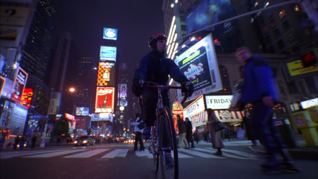 Low angle wide shot bike messenger riding through Times Square at night / NYC