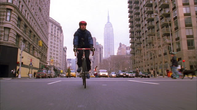 vídeos de stock e filmes b-roll de low angle wide shot bike messenger turning corner on street / empire state building in background / nyc - capacete