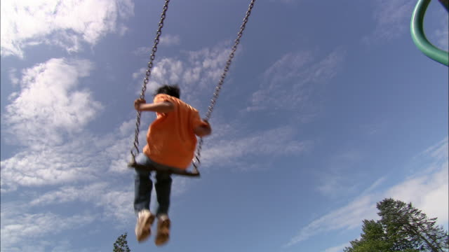 Low angle wide shot boy and girl swinging on swing set with blue sky in background