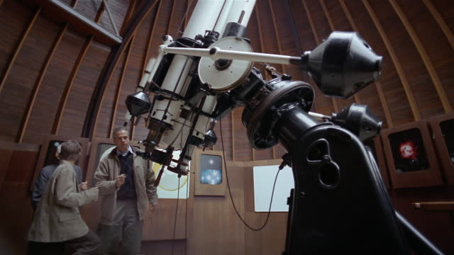 vídeos de stock e filmes b-roll de low angle wide shot boy, father and grandfather looking through telescope at observatory - astronomia