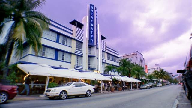 low angle wide shot breakwater hotel building w/limousine driving past / miami beach, florida - オーシャンドライブ点の映像素材/bロール