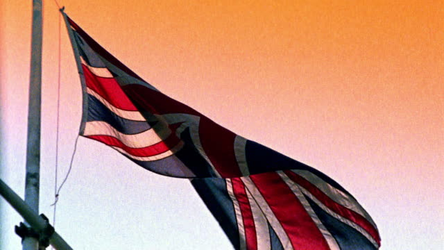 low angle wide shot british flag blowing in wind on flag pole / england - british flag stock videos and b-roll footage