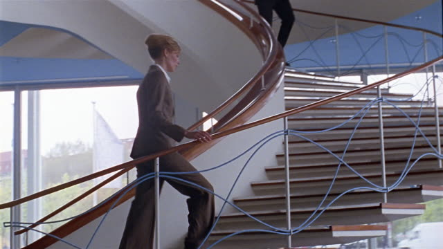 vídeos de stock, filmes e b-roll de low angle wide shot businesswoman ascending staircase / businessman greeting her on his way down - interior de casa modelo
