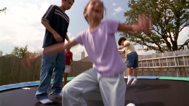 Low angle wide shot children bouncing on trampoline in backyard