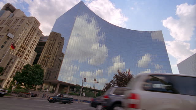 low angle wide shot clouds and sky reflected on curved glass exterior of office building / traffic in foreground / toronto - kelly mason videos stock videos & royalty-free footage