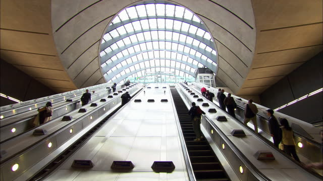 low angle wide shot commuters on escalators under glass canopy at canary wharf station/ london underground/ london - escalator stock videos & royalty-free footage