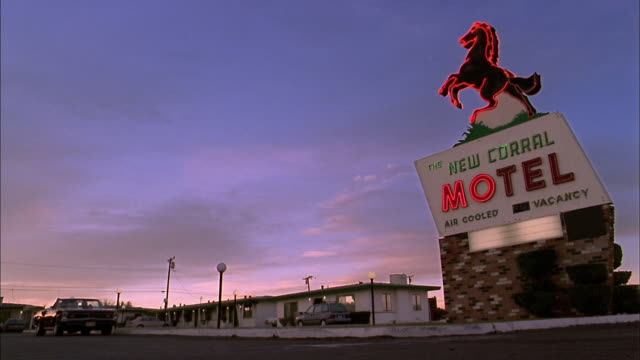 low angle wide shot convertible driving past neon motel sign at dusk - motel stock videos and b-roll footage