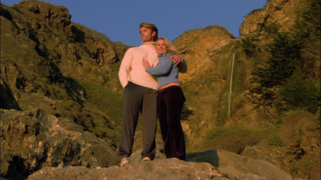 low angle wide shot couple standing in sunlight on rocky cliff/ monterey county, california - ragged point stock videos and b-roll footage