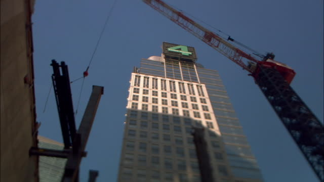 Low angle wide shot crane lowering girders to construction site below 4 Times Square building/ New York City