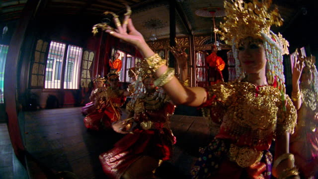 Low angle wide shot dolly shot group of women in traditional clothing dancing / Palembang, Indonesia