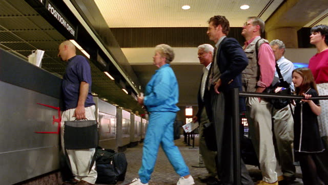 low angle wide shot dolly shot travelers crowding check in line behind bald man at airport / Phoenix Airport, AZ