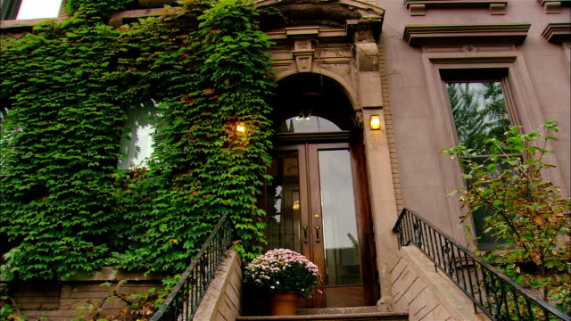 Low angle wide shot doorway to brownstone building with ivy/ Brooklyn, New York