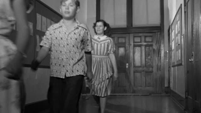 vidéos et rushes de low angle wide shot elementary school and junior high school students walking down hall toward cam / teacher behind - élève