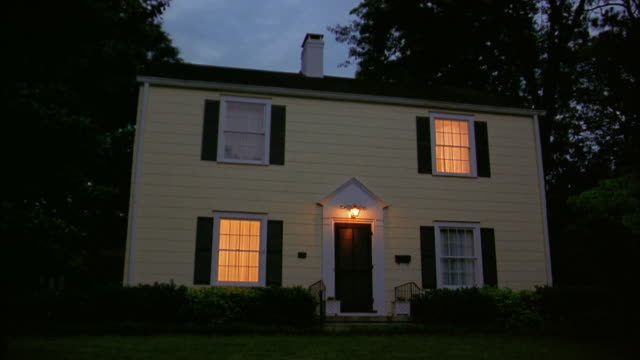 Low angle wide shot exterior of house with porch light and lights in windows on / lights in windows turning off