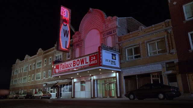 low angle wide shot exterior of palace bowl bowling alley with marquee and neon bowling pin sign / cicero, illinois - bowling alley stock videos & royalty-free footage