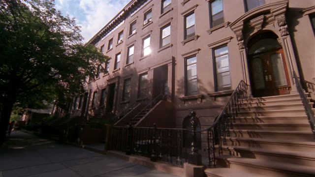 Low angle wide shot exterior of row of brownstones / Brooklyn, New York