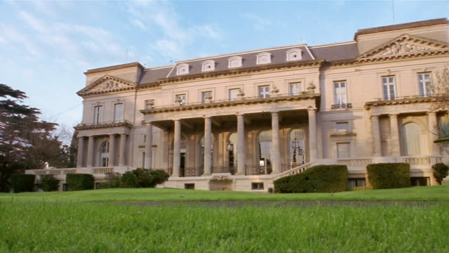 low angle wide shot facade of mansion / luxury car driving past cam - column stock videos & royalty-free footage