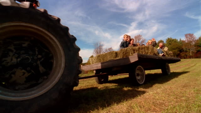 vidéos et rushes de low angle wide shot family taking a hayride on a wagon pulled by tractor - monter sur un moyen de transport