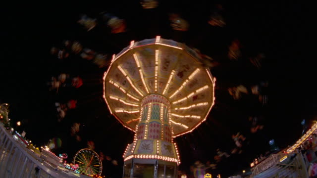 stockvideo's en b-roll-footage met low angle wide shot fast motion swing ride at canadian national exhibition at night / toronto - kelly mason videos