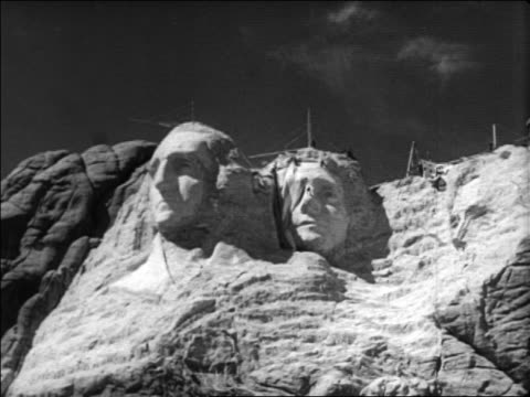 b/w 1936 low angle wide shot flag being pulled to reveal jefferson face at unfinished mt rushmore / newsreel - thomas jefferson stock videos & royalty-free footage