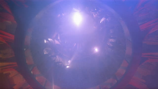 Low angle wide shot flashing lights of underbelly of UFO as it lands over CAM