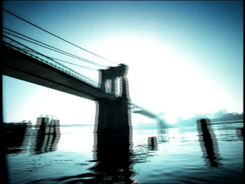 blue high contrast low angle wide shot pan from brooklyn bridge to man holding surfboard on bank of east river - high contrast stock videos & royalty-free footage