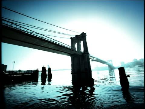 vídeos de stock, filmes e b-roll de blue high contrast low angle wide shot pan from brooklyn bridge to riverbank of east river / new york city - superexposto