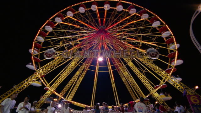low angle wide shot giant wheel at canadian national exhibition at night / fairgoers watching ride in foreground / toronto - kelly mason videos stock videos & royalty-free footage