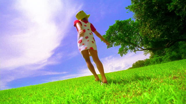 canted low angle wide shot girl wearing straw hat spinning in grassy field / florida - straw hat stock videos & royalty-free footage