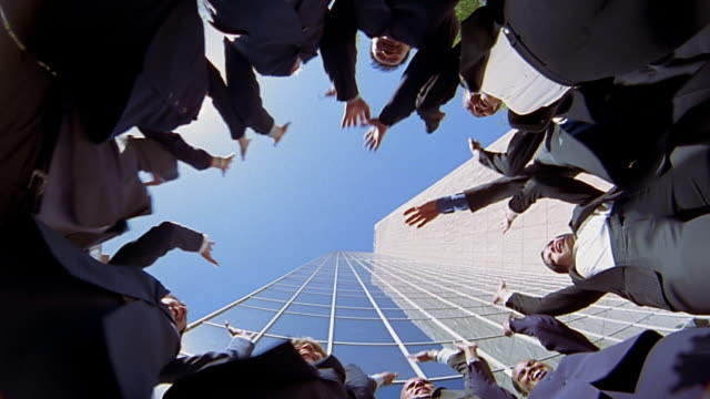 vidéos et rushes de low angle wide shot group of business people in huddle piling up hands / raising hands / cheering - serré