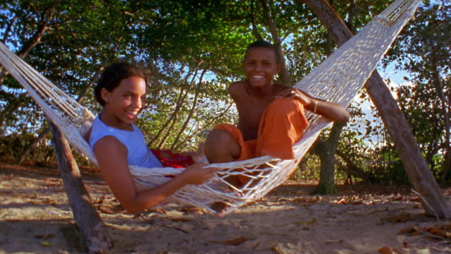 Low angle wide shot Hispanic girl and boy swinging on hammock / Dominican Republic