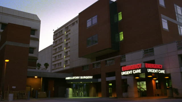 low angle wide shot hospital building with entrance to emergency room at dusk / tucson, arizona - building entrance stock videos & royalty-free footage