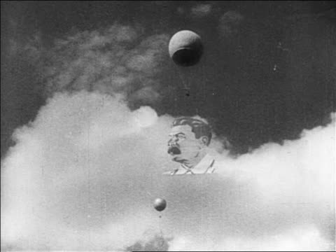 b/w 1927 low angle wide shot huge banner of stalin's face hanging from hot air balloon floating in sky / russia - 1927年点の映像素材/bロール