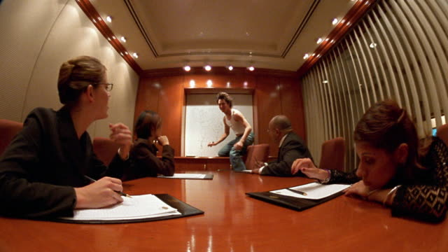 low angle wide shot irreverent young man writing on board / jumping on conference table during business meeting - music video stock videos & royalty-free footage