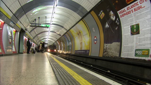 Low angle wide shot Jubilee Line train pulling into Green Park tube station / London Underground / London