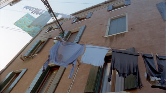 low angle wide shot laundry hanging on line in front of apartment building / venice, italy - washing line stock videos & royalty-free footage
