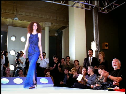 Low angle wide shot male and female models walking posing on catwalk with audience taking pictures + clapping