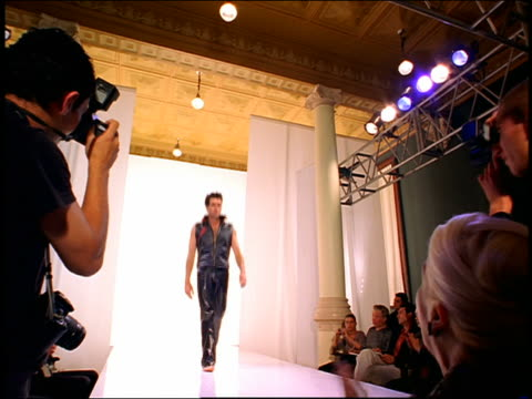 low angle wide shot male model in leather/vinyl walking on catwalk and posing for audience /video camera point of view appears - catwalk stock videos & royalty-free footage